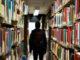 A student walking through bookshelves