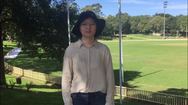 Jiani stands in the shade with a university oval in the background