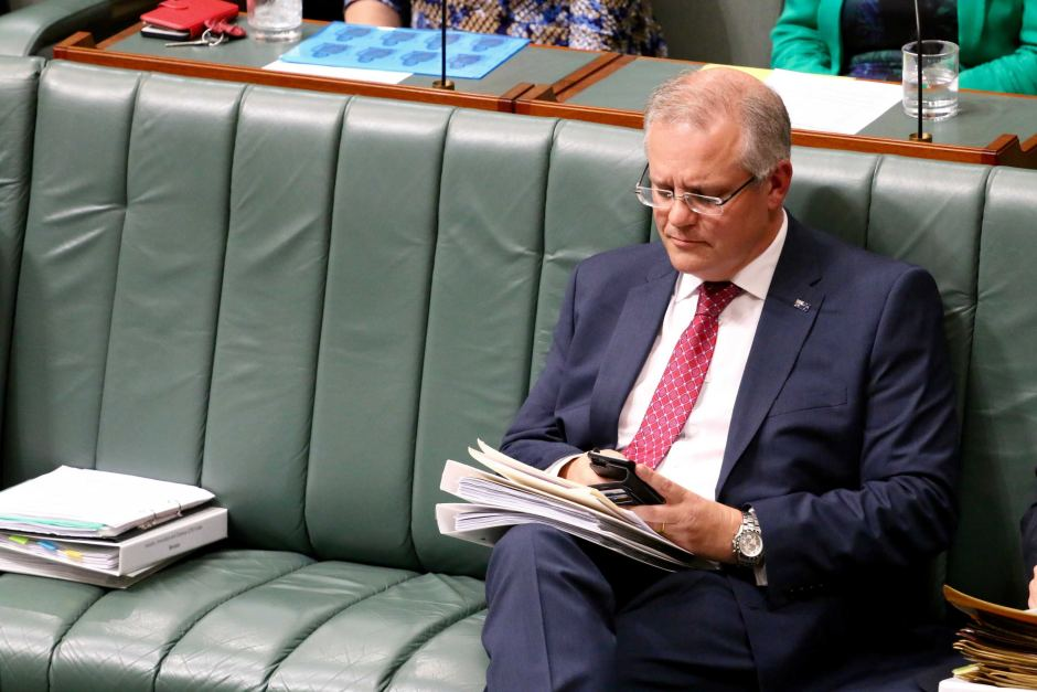 Scott Morrison is using his smart phone in parliement