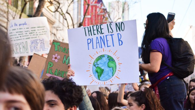 A poster calling for climate action is held by a protester