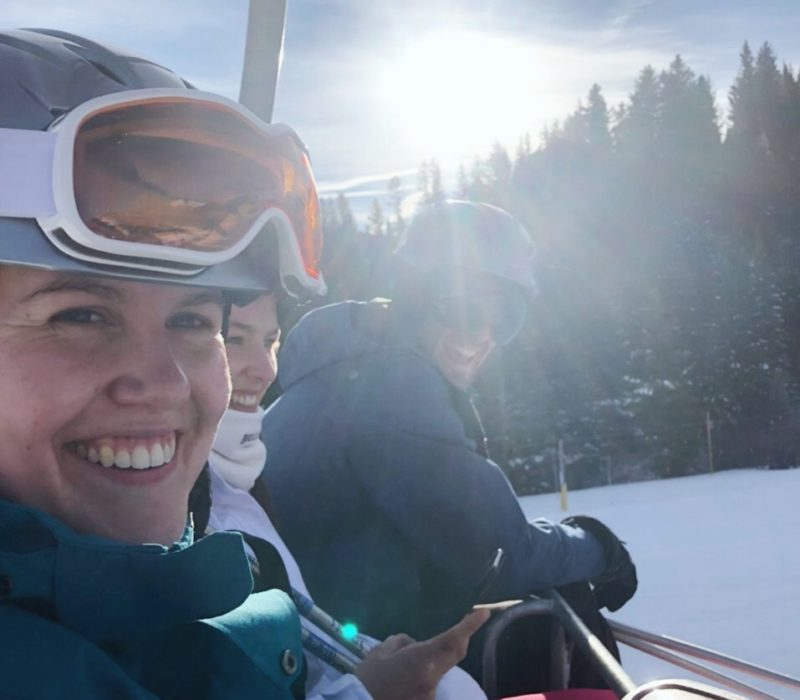 Three people on chair lift smiling