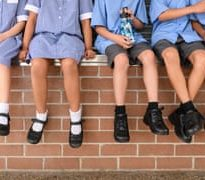 School children sitting on a wall