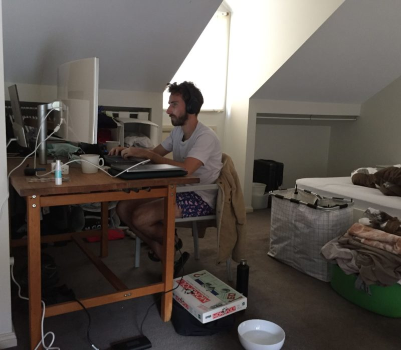 Housemate in his bedroom working on computer