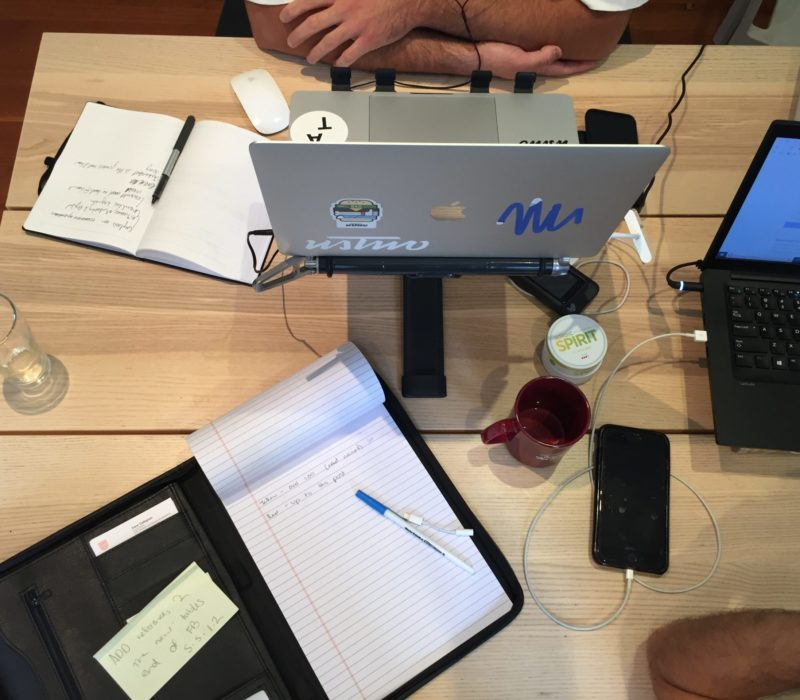 Dining table with note book, laptops, cups with coffee, chargers