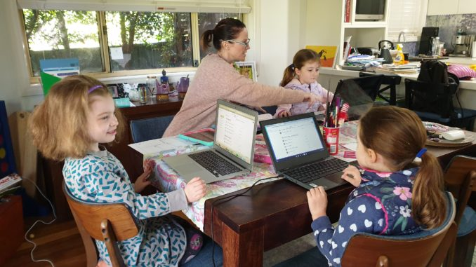 Mother working at home with three kids, all with laptops.